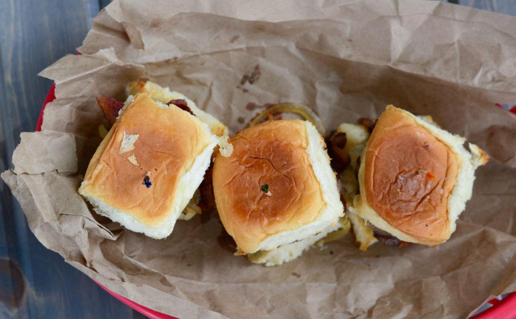 Hatch Green Chile Sliders: sweet Hawaiian roll, with a mini hamburger patty, roasted Hatch Green Chilies, sweet sautéed onions, crisp bacon, and cheese.