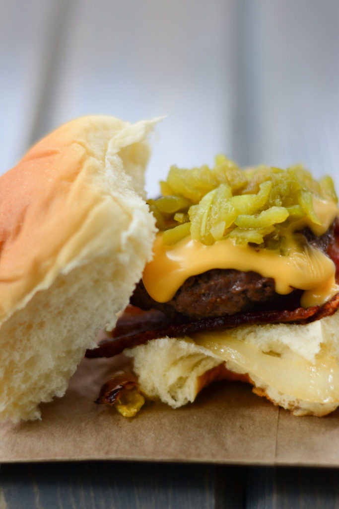 Hatch Green Chile Sliders: sweet Hawaiian roll, with a mini hamburger patty, roasted Hatch Green Chilies, sweet sautéed onions, crisp bacon, and cheese.