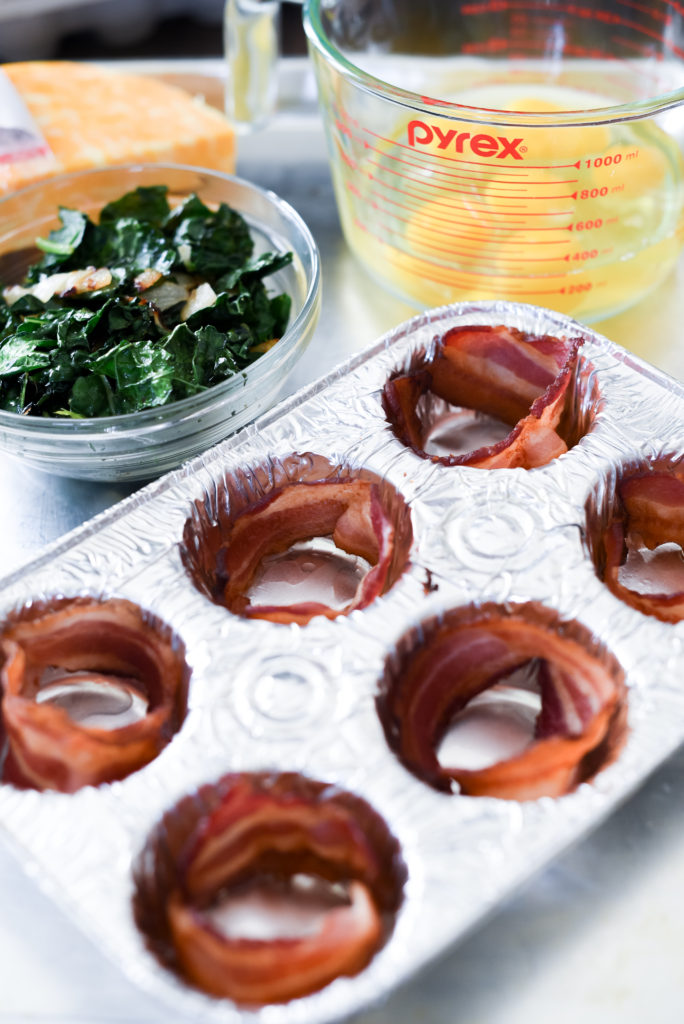 Grilled Eggs Cup perfect for a summer meal prep: Light fluffy eggs, stuffed w/ greens, caramelized onions, & cheese wrapped in a piece of bacon.