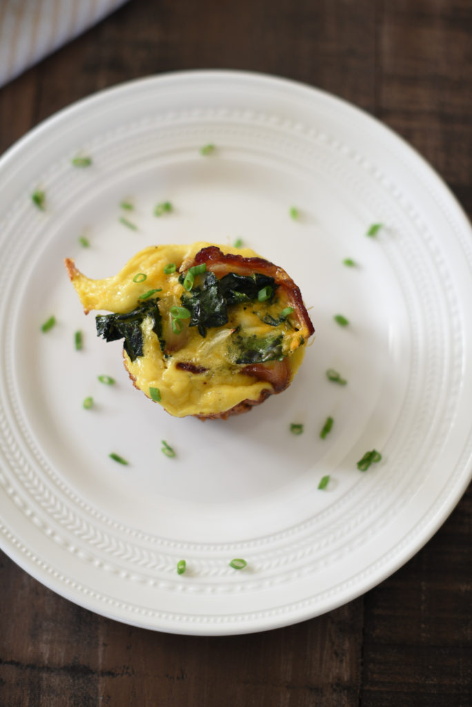 Grilled Egg Cups perfect for a summer meal prep: Light fluffy eggs, stuffed w/ greens, caramelized onions, & cheese wrapped in a piece of bacon.