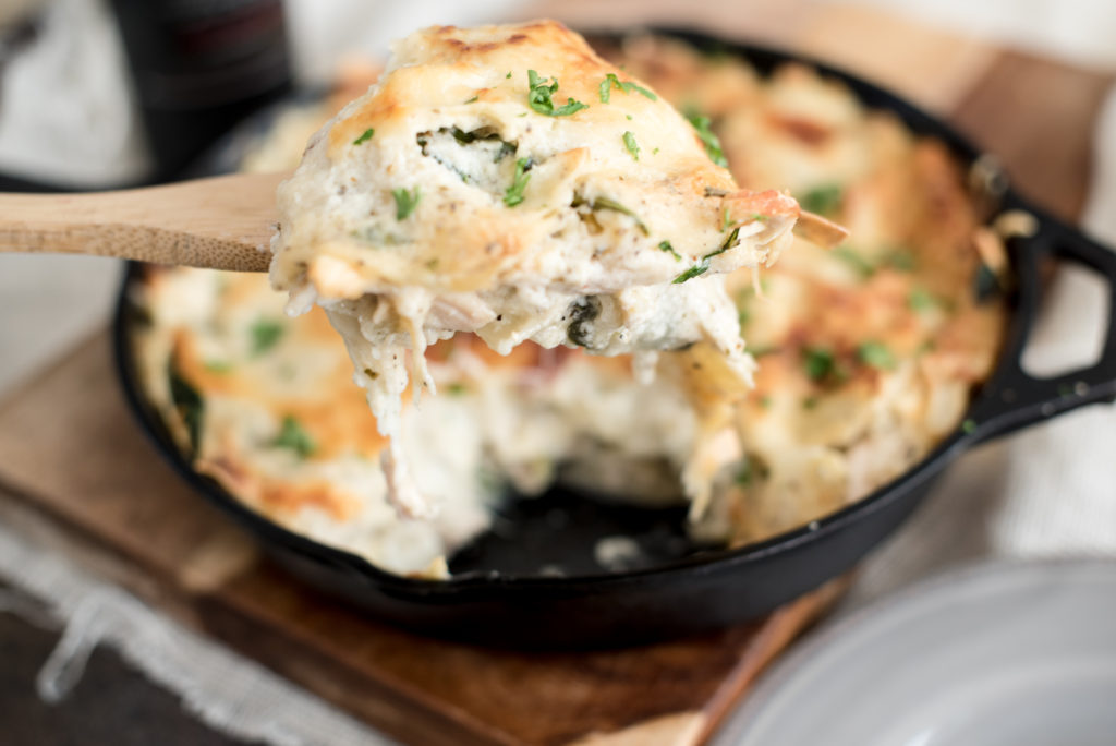 Chicken Alfredo Skillet Lasagna with a homemade garlic cream sauce, shredded chicken, fresh herbs, shredded cheese, all layered in a skillet and baked!