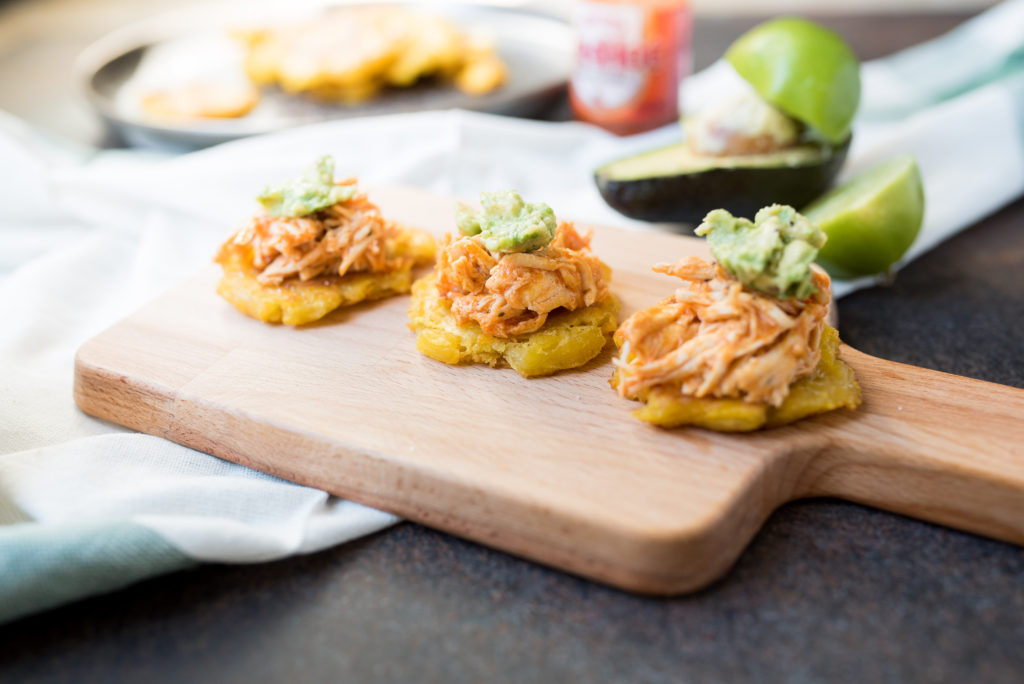 Buffalo Chicken Tostones: Crispy pan- fried plantains topped with shredded buffalo chicken, and smashed avocado with a squeeze of lime juice!