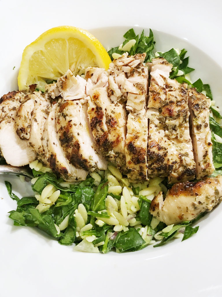 Greek marinated chicken served over a warm orzo and spinach salad with salty feta and red onion drizzled with a sweet/ tart red wine vinaigrette.