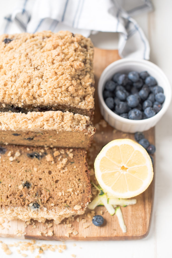 loaf of zucchini bread with oatmeal streusel on wooden cutting board with blueberries and half a lemon next to it