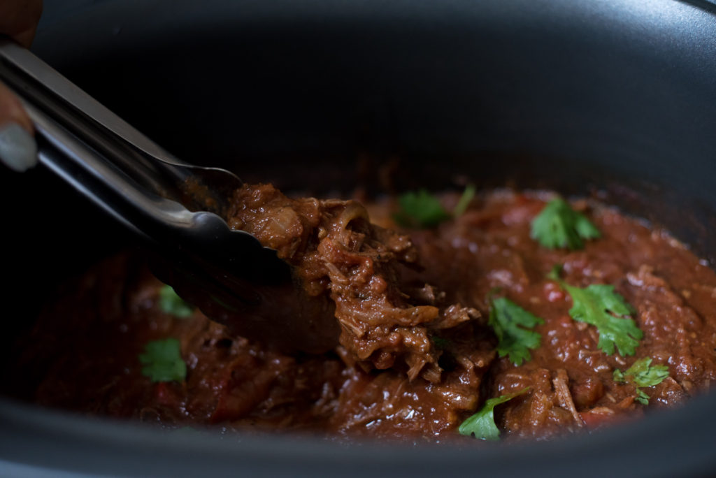 Slow Cooker Ropa Vieja: Savory shredded beef left to simmer in a delicious tomato based sauce best served over rice with a side of sweet plantains!